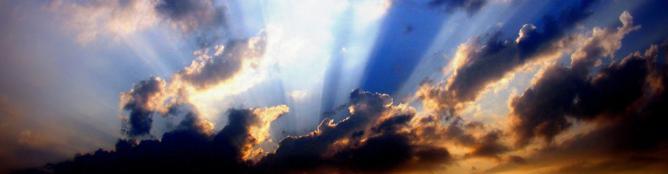 Image of Clouds and sun rays over a blue sky