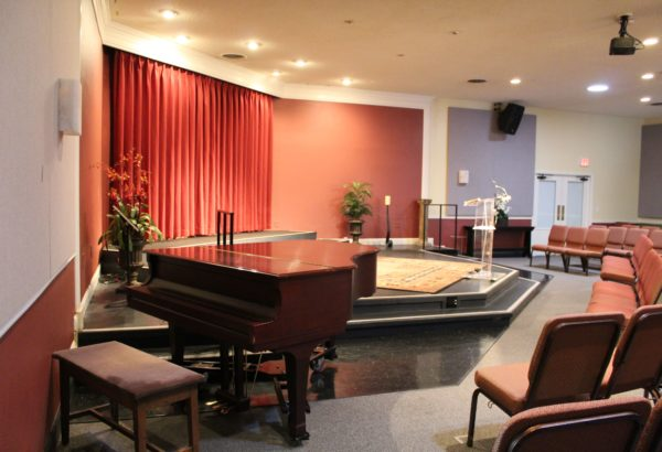 Warm and inviting photo of Center for SPiritual Living, Chico's stage room with mini grand piano and stage view