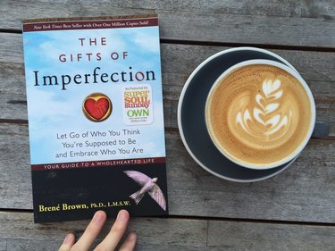 Image of the Gifts of Imperfection book on a wooden bench next to a coffee latte
