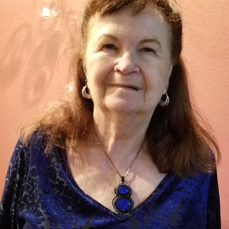 Portrait of Practitioner Sherry wearing a deep royal blue top and matching necklace