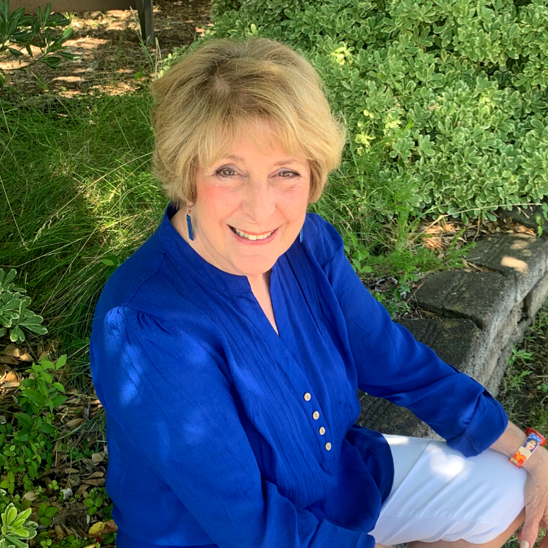 Portrait of Practitioner Connie wearing blue and sitting outside