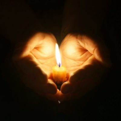 Hands holding a wax candle. Candlelight. Stock image of hands cupping a lite candle.