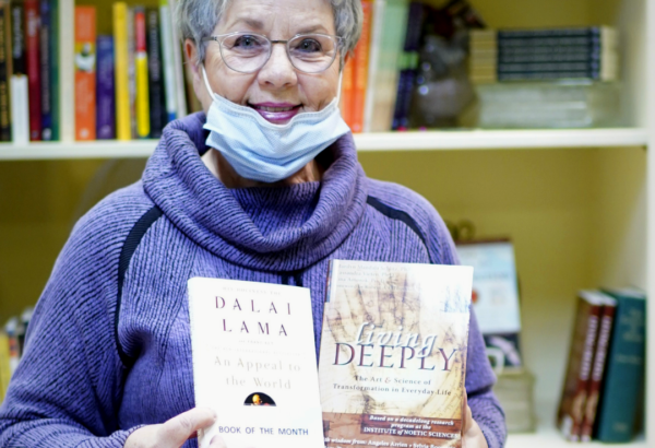 Image of older woman wearing a purple sweater holding new thought books at Center for Spiritual Living Chico s in house Bookstore social distancing bookstore