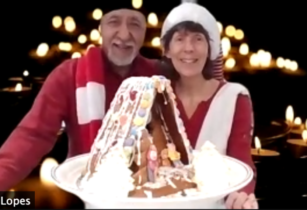 Screen shot of older couple holding up the gingerbread house they just made online in a Christmas zoom event