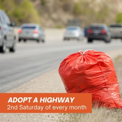 image of trash being picked up in an orange trash bag by a busy highway