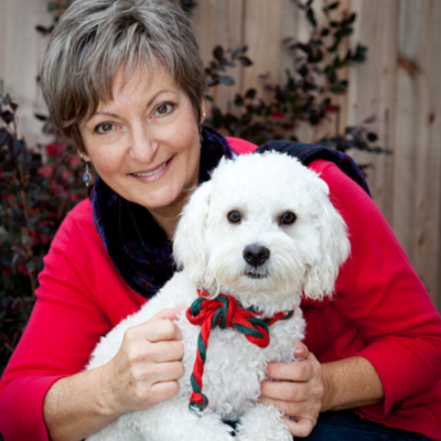 Portrait of Rev Christine Jeffers wearing a red coat with her dog