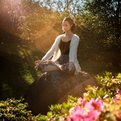 Woman sitting on a rock outside meditating. with flowers blooming next to her