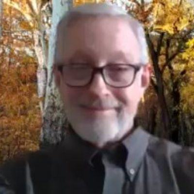 Screenshot of john boyles online guided meditation for CSL man with glasses smiling