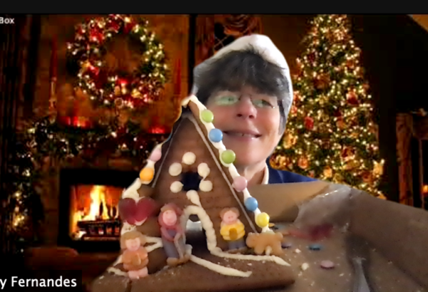 image on online gingerbread house building in zoom. Image of woman holding up gingerbread house from an online event