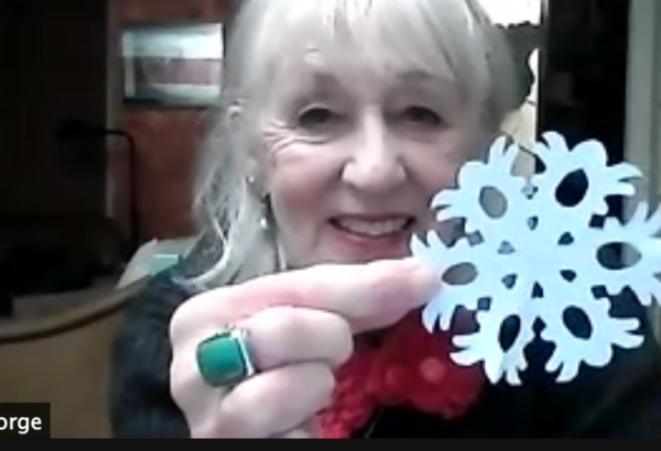 photo of online event of woman making cut outs of paper snow flakes in a zoom event for Christmas