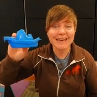Screen capture of musician Amber Darland on her youtube channel videos for kids toddlers + preschool music class online image of Amber holding up a blue toy boat for kids