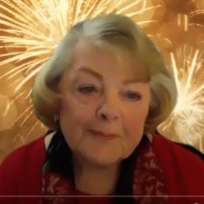 Screen shot image of an end of the year guided meditation. image of older woman in zoom giving a meditation service wearing read with a short bob hair cut.